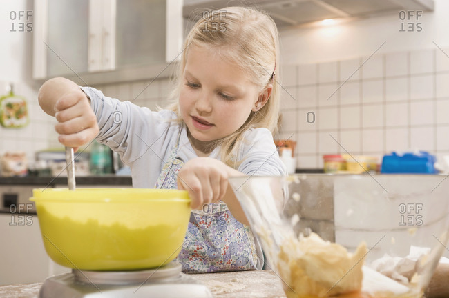 Girl mixing flour in bowl for cookies