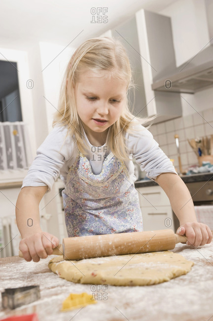 Girl rolling dough for cookies