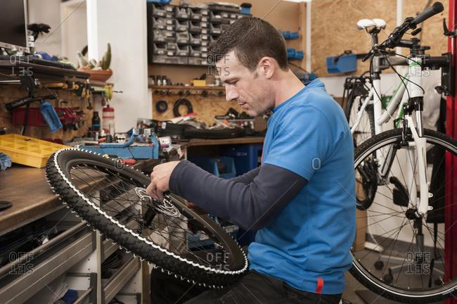 Man repairing bicycle in workshop