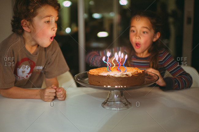 Twins blowing out the candles on their birthday cake