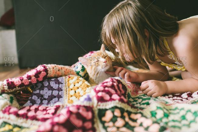 Little girl scratching a cat under the chin