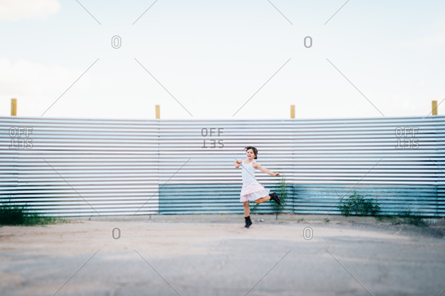 Girl frolicking outdoors by corrugated iron wall