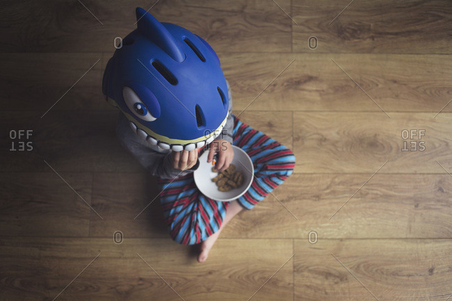 Young boy eating cookies in a shark helmet