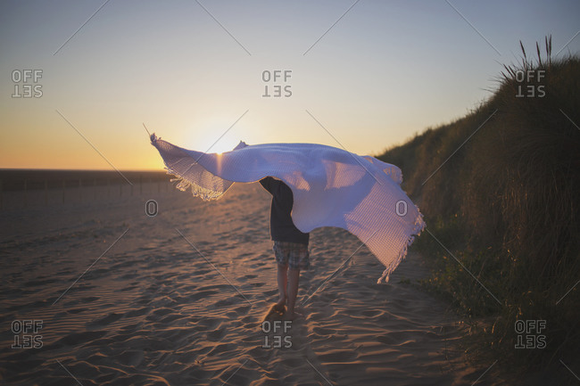 Young boy walking on a sandy beach with a blanket at sunset