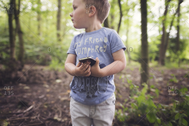 Young boy holding a smartphone in a forest