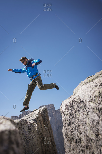 Hiker leaping across a crevice, Wind River Range