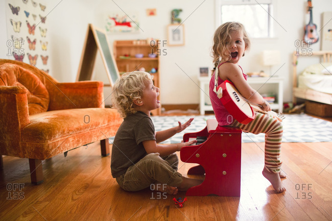 A girl and boy play musical instruments together