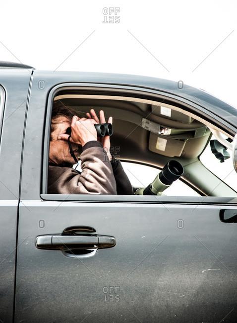 Man looking trough a binocular in a car