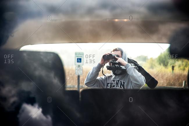 Man looking trough a binocular at a car
