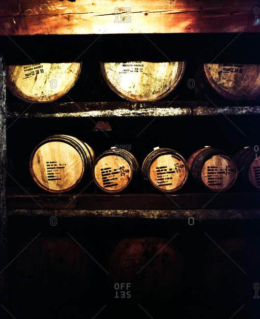 Barrels of different types of bourbon in a distillery