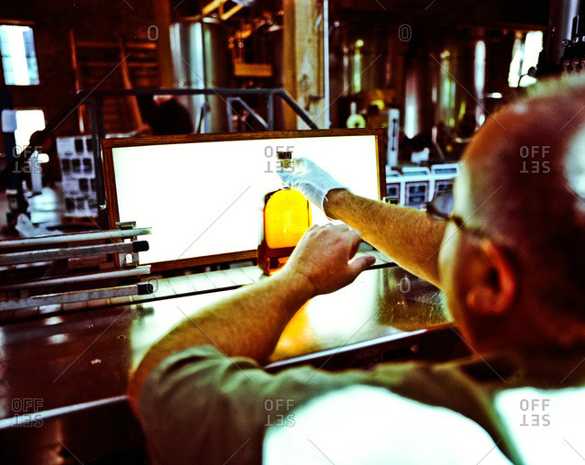 Man checking the clarity of bourbon in a distillery