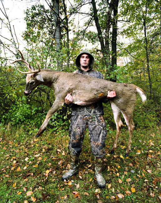 Pond Eddy, New York - February 24, 2012: Young man holding a 7 point buck shot with an arrow