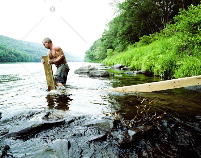 Pond Eddy, New York - February 24, 2012: Man building an eel weir in Pond Eddy, New York