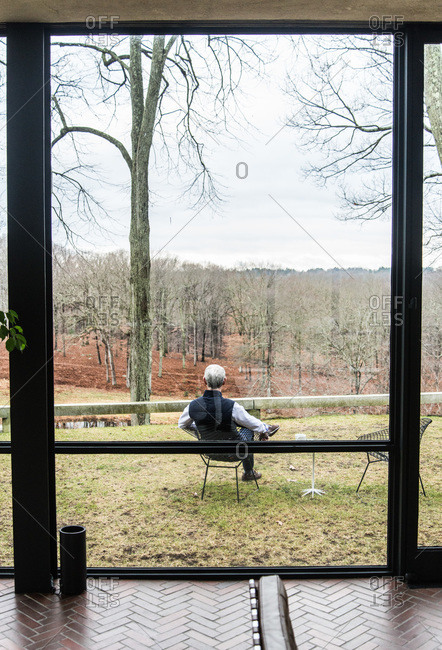 New Canaan, Connecticut - May 10, 2000: Man sitting outside the Glass House in New Canaan, Connecticut
