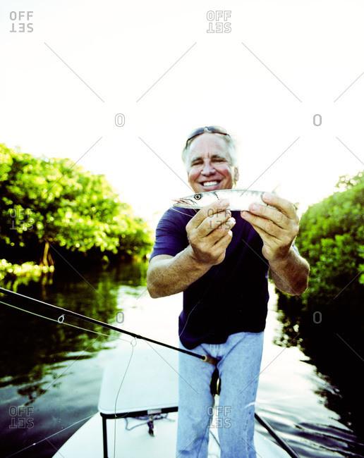 Key West, Florida - February 20, 2012: Fishing guide Jeffrey Cardenas with baby barracuda