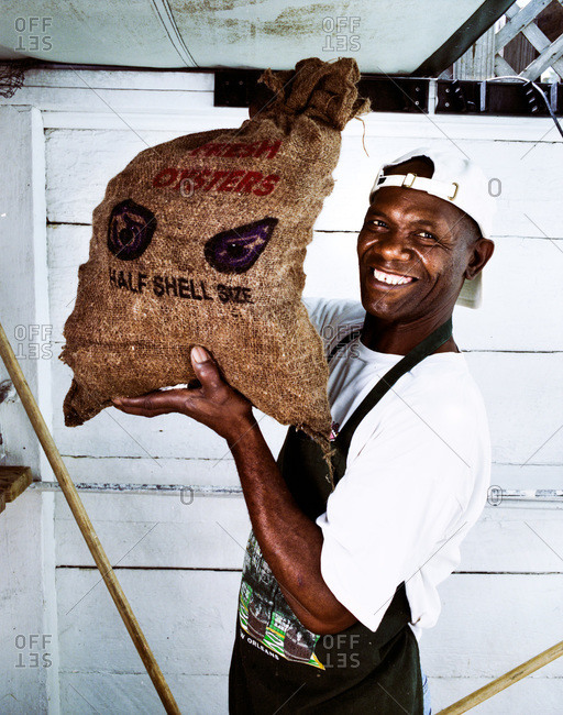New Orleans, Louisiana - February 26, 2012: Portrait of a  master oyster shucker holding a bag of oysters