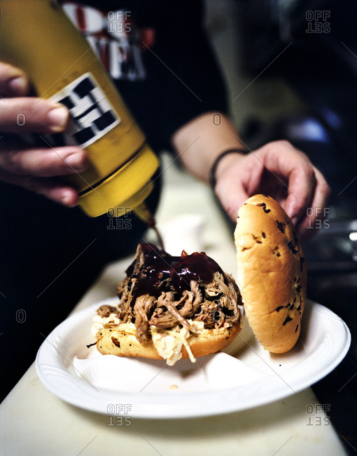 Person adding special hog heaven sauce to a pulled pork sandwich