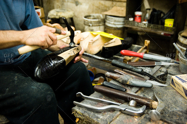 Shoemaker hammering a shoe