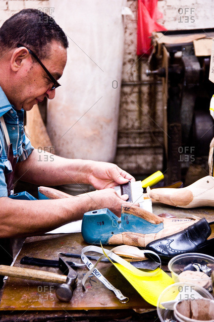 New York, New York - June 7, 2012: Shoemaker making shoes in a workshop