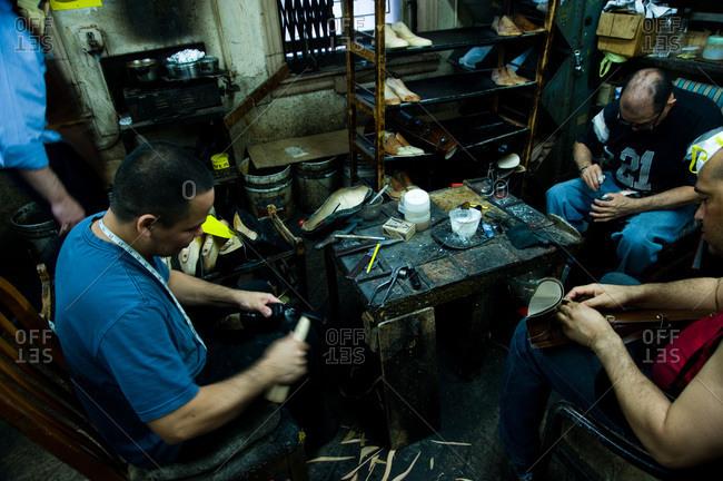 New York, New York - June 7, 2012: Men working in a shoemaker's workshop