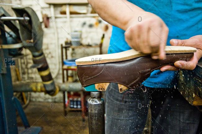 Shoemaker polishing the sole of a shoe