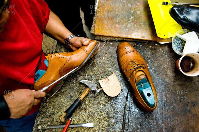Shoemaker making a wingtip shoe in a workshop