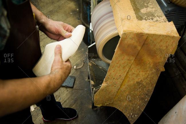 Shoemaker polishing a wooden shoe tree