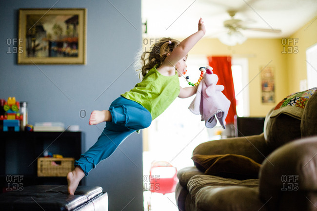 Young girl jumping over to a couch