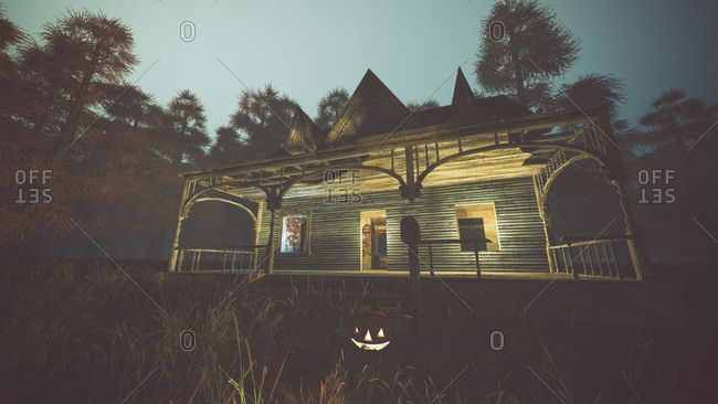 Abandoned house with halloween pumpkin and lights on field in misty autumn forest at dusk