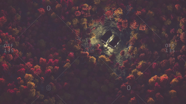 Aerial of abandoned house with lights in autumn forest with mist