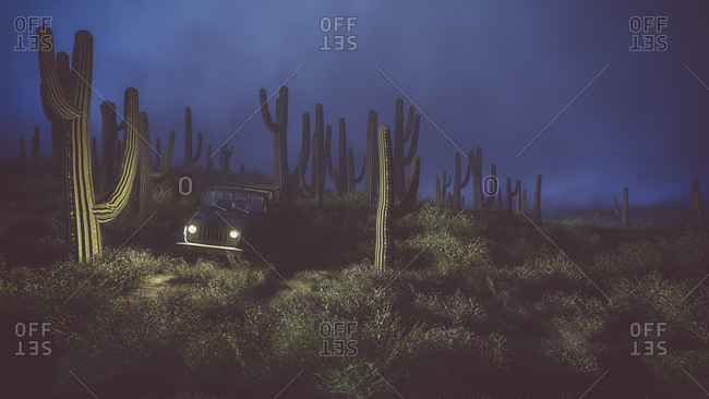 Lost off road car with lights on standing in cactus desert at night