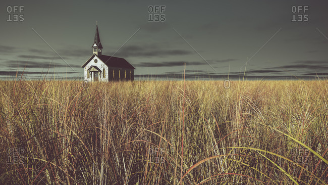 Old abandoned white wooden church on prairie with dark cloudy sky