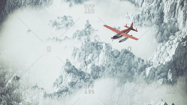 Aerial of red airplane flying over snow mountain landscape in clouds
