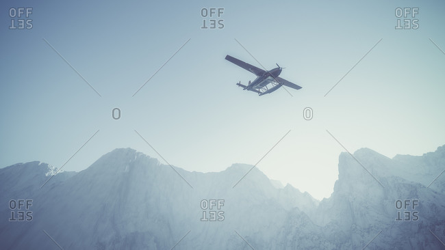 Red airplane flying over misty snow mountain landscape with blue sky
