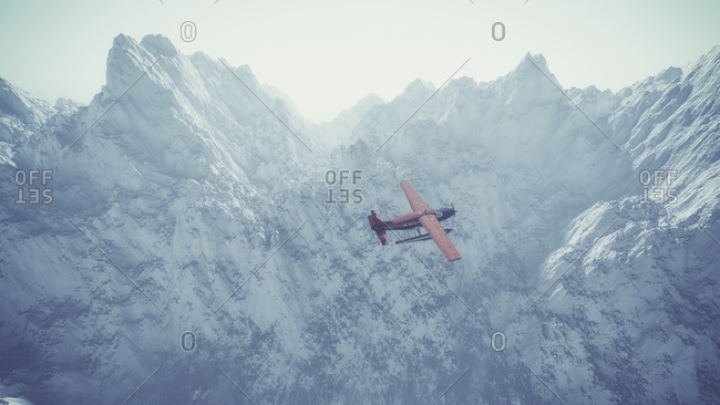 Aerial of red airplane flying over misty snow mountain landscape with blue sky