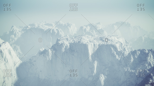 Aerial of misty snow mountain landscape with blue sky