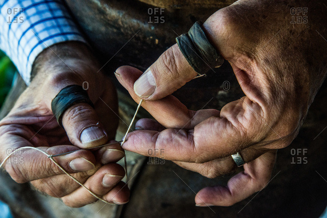 Craftsman locking a needle for stitching leather