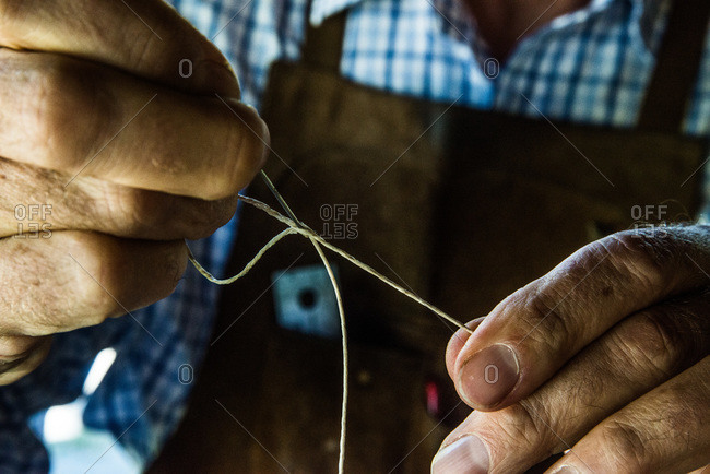 Close up of leather craftsman locking a needle for stitching