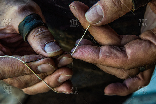 Leather craftsman locking a needle for stitching