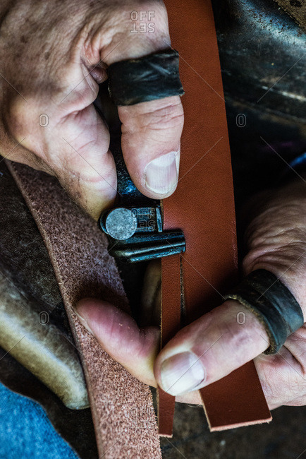 Artisan cutting a piece of leather