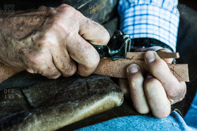 Craftsman cutting a piece of leather