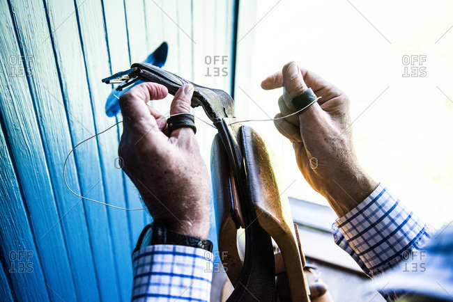 Artisan sewing a leather belt