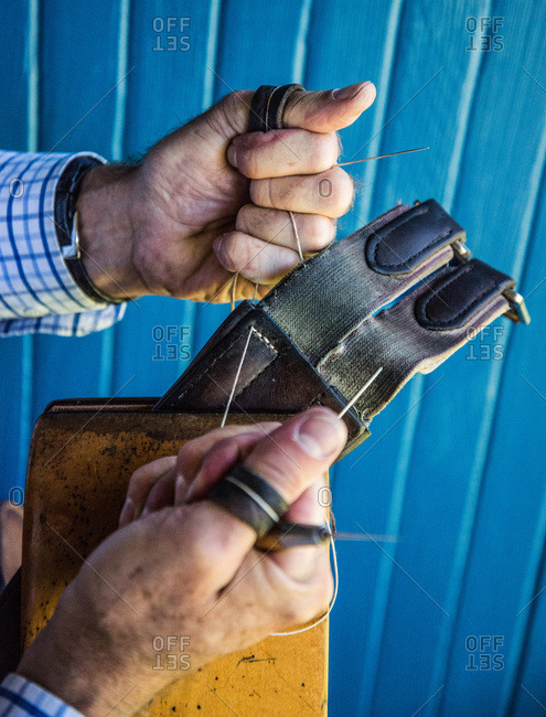 Craftsman sewing a leather belt