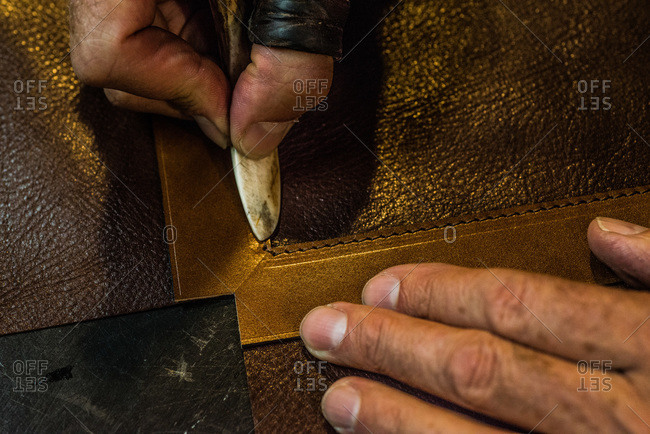 Artisan pressing a craft tool on a piece leather