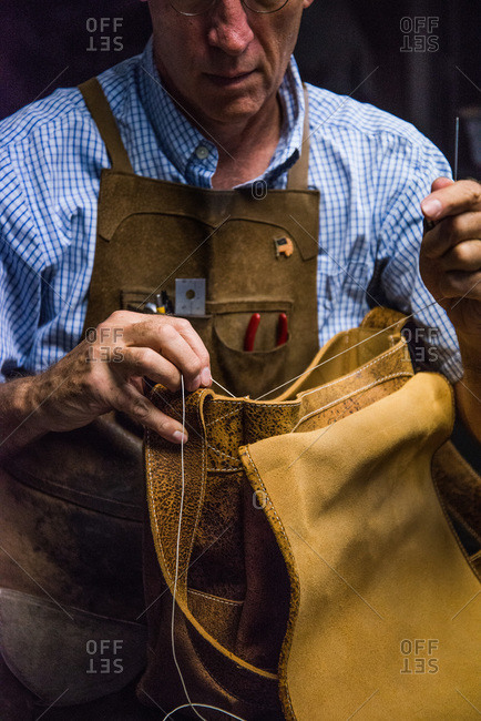 Crozet, Virginia - February 8, 2000: Chuck Pinnell sewing a leather bag
