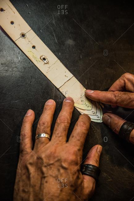 Craftsman measuring a belt sample on a table
