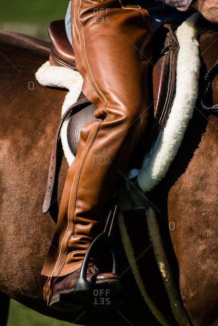 Man wearing leather riding chaps on a horseback