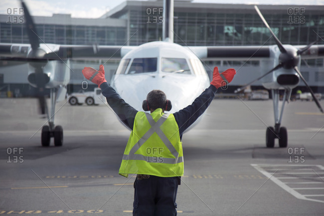 Member of ground crew guides an airplane