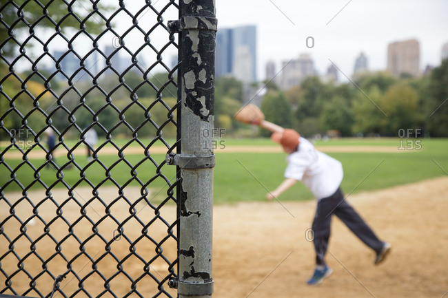 A boy plays baseball in Central Park