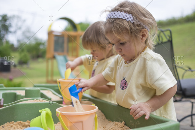 Twin toddlers playing in a sandbox